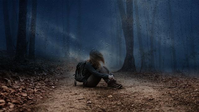 دختر تنها نشسته در تاریکی جنگل
