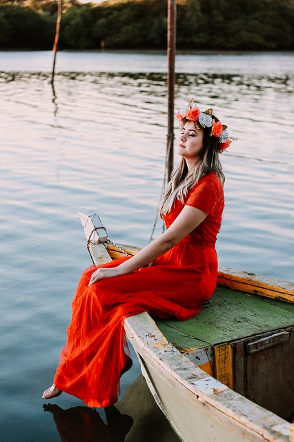دختر قرموز پوش نشسته کنار آب