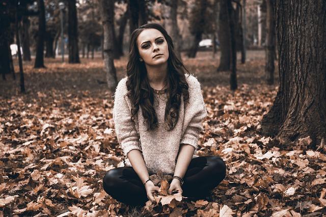 دختر نشسته در برگ های پاییز