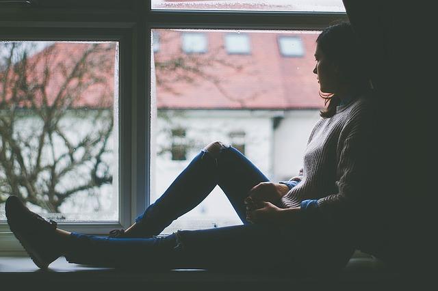 دختر نشسته کنار دیوار