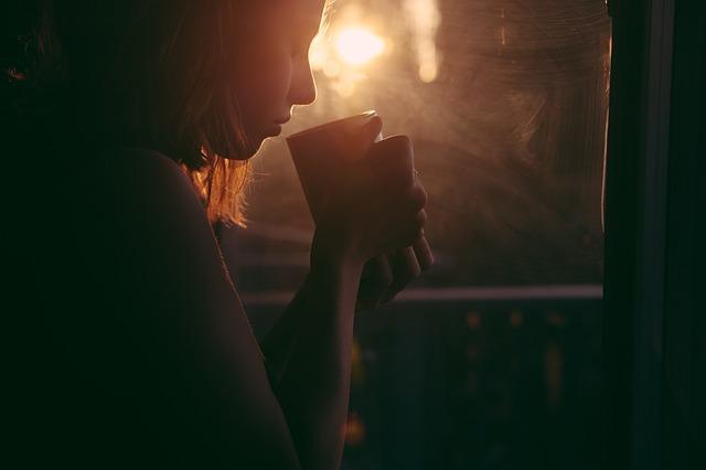 دختر کنار پنجره در حال نوشیدن
