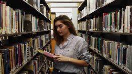 دختر در حال دیدن کتاب های کتابخانه